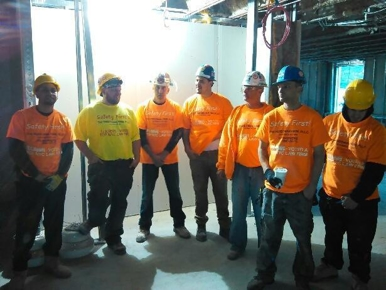 workers wearing Perecman Firm construction shirts